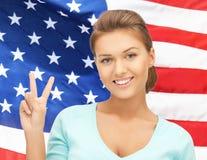 Молодая женщина показывая победу или знак мира Стоковая Фотография RF