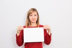 Молодая женщина показывая чистый лист бумаги Стоковые Фото
