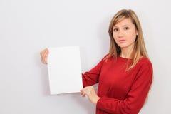 Молодая женщина показывая чистый лист бумаги Стоковые Изображения