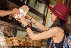 Молодая женщина покупает свежие печенья на рынке хлебопекарни стоковые фото