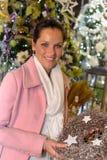 Молодая женщина покупая блестящий венок рождества Стоковые Изображения