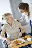 Молодая женщина помогая старшей женщине в кресло-коляске Стоковое Фото