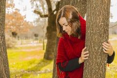 Молодая женщина портрета красивая нося красную плащпалату шерстей смотря d Стоковая Фотография