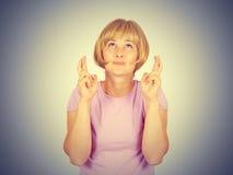Молодая женщина портрета крупного плана надеющийся пересекая ее пальцы Стоковые Изображения RF