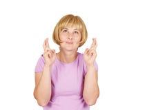 Молодая женщина портрета крупного плана надеющийся пересекая ее пальцы Стоковая Фотография RF