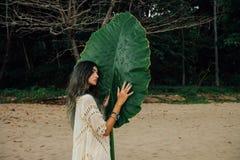 Молодая женщина портрета привлекательная на дереве больших зеленых лист предпосылки тропическом Стоковые Изображения