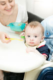Молодая женщина подавая ее младенец от ложки с соусом яблока Стоковая Фотография RF