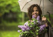 Молодая женщина под зонтиком с букетом сирени в руке во время дождя Стоковая Фотография RF