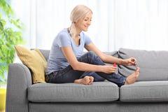 Молодая женщина полируя ее toenails и усмехаться Стоковое фото RF