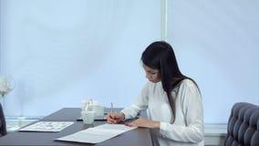 Молодая женщина подписывая официально документы сидя на таблице кафа видеоматериал