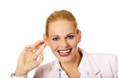 Молодая женщина подслушивает переговор и смеяться над стоковая фотография rf