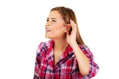Молодая женщина подслушивая переговор стоковые фото