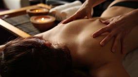 Молодая женщина получая задний массаж в салоне курорта Руки крупного плана masseur акции видеоматериалы