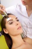 Молодая женщина получая обработку маски кожи красоты на ее стороне с Стоковое фото RF