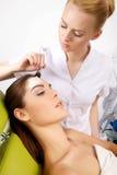 Молодая женщина получая обработку маски кожи красоты на ее стороне с Стоковое Изображение RF