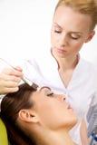 Молодая женщина получая обработку маски кожи красоты на ее стороне с Стоковые Фотографии RF