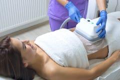 Молодая женщина получая обработку cryolipolyse в косметическом шкафе Стоковая Фотография RF