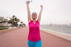 Молодая женщина празднуя успешный бег тренировки стоковое изображение