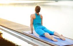 Молодая женщина практикуя верхнее представление йоги собаки облицовки Стоковое Фото