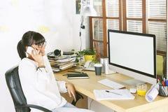Молодая женщина предпринимателя используя мобильный телефон на домашнем офисе Стоковые Фотографии RF