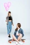 Молодая женщина представляя воздушные шары к милой подруге сидя на скейтборде Стоковое фото RF