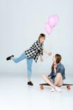 Молодая женщина представляя воздушные шары к милой подруге сидя на скейтборде Стоковая Фотография RF