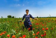 Молодая женщина представляя в красном поле маков Стоковые Изображения
