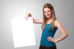 Молодая женщина представляя космос экземпляра белой бумаги Стоковые Изображения RF