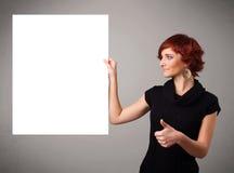 Молодая женщина представляя космос экземпляра белой бумаги Стоковая Фотография