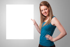 Молодая женщина представляя космос экземпляра белой бумаги Стоковое Фото