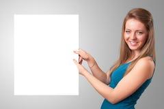 Молодая женщина представляя космос экземпляра белой бумаги Стоковые Изображения
