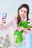 Молодая женщина представляя на ее камере телефона с цветками Стоковые Изображения