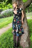 Молодая женщина представляя на дереве стоковое изображение