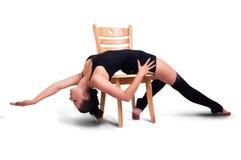 Молодая женщина представляя на стуле Стоковое Изображение RF