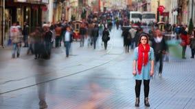 Молодая женщина представляя, оживленная улица, люди идя вокруг, 4K сток-видео