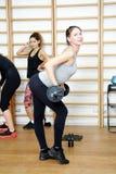 Молодая женщина представляя тренировку с баром в спортзале Стоковые Фото