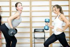 Молодая женщина представляя тренировку с баром и гантель в спортзале Стоковые Фотографии RF