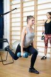 Молодая женщина представляя тренировку с гантелями в спортзале Стоковое фото RF