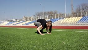 Молодая женщина привлекательного active подходящая делает представление простирания йоги на траву огромного стадиона зеленую разм сток-видео