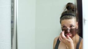 Молодая женщина прикладывая лицевую маску chocotate акции видеоматериалы