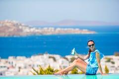 Молодая женщина прикладывая солнцезащитный крем на ее ногах, сидя на краю городка Mykonos предпосылки бассейна старого в Европе Стоковые Изображения
