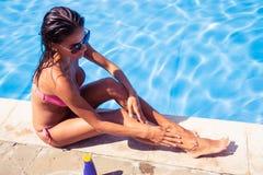 Молодая женщина прикладывая сливк солнца Стоковые Изображения RF