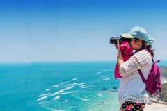 Молодая женщина принимает фото моря на ясный день неба стоковое изображение rf