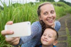 Молодая женщина принимая автопортрет с ее сыном в парке Стоковая Фотография