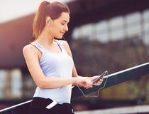 Молодая женщина принимая пролом от работать снаружи с мобильным телефоном стоковое фото rf