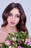 Молодая женщина при глаза серого цвета и длинные коричневые волосы держа розовую подачу Стоковые Изображения RF