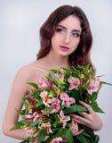 Молодая женщина при глаза серого цвета и длинные коричневые волосы держа розовую подачу Стоковое Фото