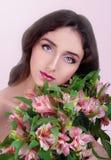 Молодая женщина при глаза серого цвета и длинные коричневые волосы держа розовую подачу Стоковые Изображения
