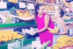 Молодая женщина при девушка покупая различные плодоовощи в продовольственном магазине стоковая фотография