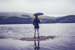 Молодая женщина при зонтик стоя в озере стоковое изображение
